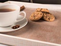 Vit kopp te på magasinet med kakor och cikorien Arkivbild