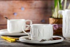 Vit kopp te på tabellen avslappnande teakvinna för cocktail party Arkivbild