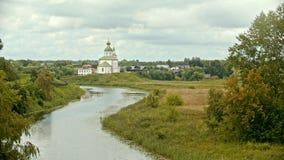 Vit kristen kyrka i byn - vattenliten vik på en förgrund - Suzdal, Ryssland lager videofilmer