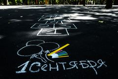 Vit krita på den svarta asfaltinskriften i ryss September 1 gul linje, färgrika markörer, målade bollar, hoppa hage stock illustrationer