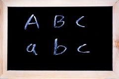 Vit krita som är skriftlig på en svart tavla Arkivbilder