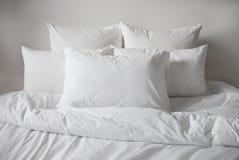 Vit kuddar, duntäcke och duvetcase i en säng Slapp fokus royaltyfri fotografi