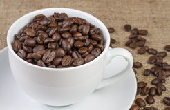 Vit kuper av kaffebönor på hessian royaltyfri fotografi