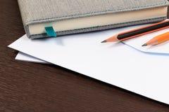 Vit kuvert och anteckningsbok med blyertspennan Arkivbild