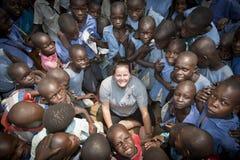 Vit kvinna som omges av afrikanska barn Arkivfoto