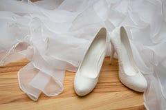 Vit kvinnor som gifta sig skor med häl med modeller i formen av blommor på bakgrunden av bröllopsklänningen arkivbild