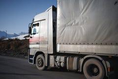 Vit kylde lastbilen på vintervägen på bakgrund av bergen Royaltyfria Foton