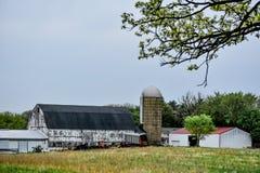 Vit ladugård med silon och uthuset Wisconsin royaltyfri fotografi