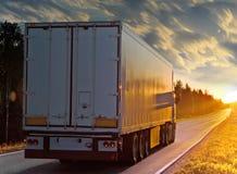 Vit lastbil på den lantliga vägen i afton royaltyfri bild