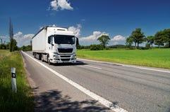 Vit lastbil på vägen i ett lantligt landskap Royaltyfria Bilder