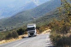 Vit lastlastbil som kör på bergvägen Royaltyfri Foto