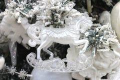 Vit leksakhäst för julpynt på ett snöträd med girlander royaltyfri foto
