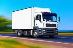 Vit leveranslastbil på vägen Arkivbild