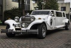 Vit limousine som tas från vänstersidaframdelen Arkivfoton