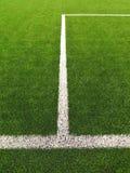 Vit linje på konstgjort gräsfält på fotbolllekplats Detalj av ett kors av målade vita linjer i ett fotbollfält Fotografering för Bildbyråer