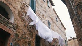 Vit linne som hänger på torken under fönstren lager videofilmer
