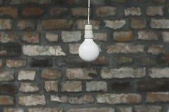 Vit ljus kula framme av tegelstentexturväggen Arkivfoto