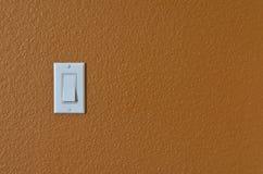 Vit ljus strömbrytare på den orange väggen Arkivbild