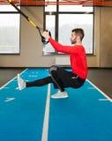 Vit lockig skäggig sportig man som övar med konditionremmar i idrottshall Royaltyfria Foton