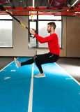 Vit lockig skäggig sportig man som övar med konditionremmar i idrottshall Arkivfoton