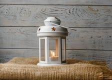 Vit lykta med en tänd stearinljus bredvid en gåvaask Royaltyfria Foton