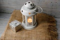 Vit lykta med en tänd stearinljus bredvid en gåvaask Royaltyfri Foto