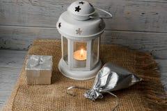Vit lykta med en tänd stearinljus bredvid en gåvaask Royaltyfri Bild