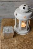 Vit lykta med en tänd stearinljus bredvid en gåvaask Royaltyfria Bilder