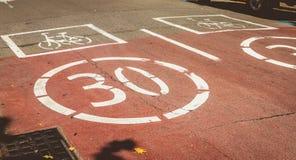 Vit målarfärg på en röd väg som indikerar närvaro av en cykel och ett f Arkivfoton