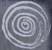 Vit målarfärgspiral på den gråa grungestenväggen Arkivbild