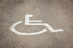 Vit målat rullstolsymbol på trottoar i parkeringsstall Royaltyfri Fotografi