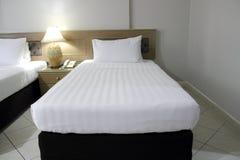 Vit madrass och svart säng arkivbilder