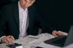 Vit man som arbetar i ett kontor med dokument Chefen g?r rapporten och fyller in f?rklaringen Aff?rsman p? arbete in arkivbild