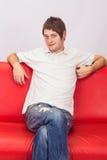 Vit mansammanträde på en röd soffa Royaltyfri Fotografi