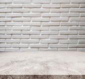 Vit marmorstentabletop, med bakgrund för textur för vägg för defocustegelsten vit arkivfoto