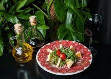 Vit maträtt med carpaccio av nötkött på den svarta tabellen Arkivbilder