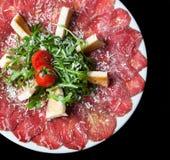 Vit maträtt med carpaccio av nötkött på den svarta tabellen Royaltyfria Bilder