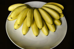 Vit maträtt med en solfjäderformig grupp av små unpeeled mogna bananer Arkivfoto
