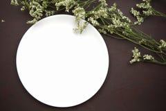 Vit maträtt med vita blommor på brun läderbakgrund Fotografering för Bildbyråer