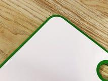 Vit med den gröna skärbrädan ligger på en trätabell Använt i köket Närbild fotografering för bildbyråer