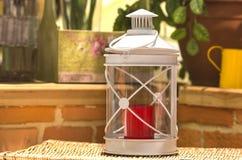 Vit metall med glasväggljusstaken med en röd stearinljus inom på en bakgrund för tegelstenvägg royaltyfria bilder