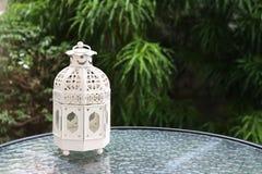 Vit metall som är lattern i retro design på spegeltabellen i trädgård Fotografering för Bildbyråer