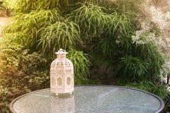 Vit metall som är lattern i retro design på spegeltabellen i trädgård Arkivbild