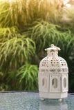 Vit metall som är lattern i retro design på spegeltabellen i trädgård Arkivfoto
