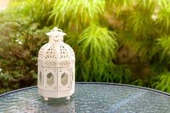 Vit metall som är lattern i retro design på spegeltabellen i trädgård Royaltyfri Foto