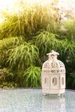 Vit metall som är lattern i retro design på spegeltabellen i trädgård Arkivfoton