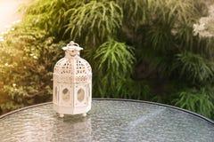 Vit metall som är lattern i retro design på spegeltabellen i trädgård Royaltyfri Bild