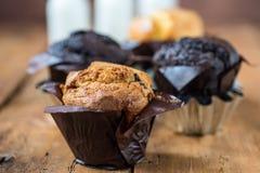 Vit mjölkar och choklad bakade muffin - träbakgrund Royaltyfri Foto