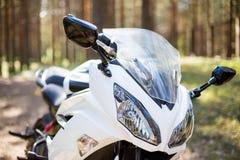 Vit motorcykel, styrninghjul soligt väder i skogen med mototurism och rekreationbegrepp pannlampor av a royaltyfria bilder