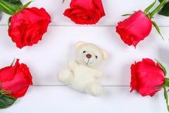 Vit nallebjörn som omges av rosa rosor på en vit trätabell Mall för mars 8, mors dag, valentin dag Fotografering för Bildbyråer